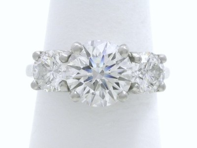 Round brilliant cut diamond three-stone engagement ring with platinum classic basket style mounting