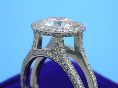 Round brilliant cut diamond bezel set in Bez Ambar designer mounting with knife-edge pave frame and on top and outside of split shank