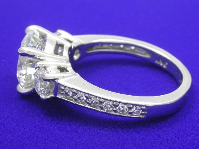 Round brilliant cut diamond prong set in a platinum three-stone mounting with two round brilliant side diamonds and round melee channel-set down the shank