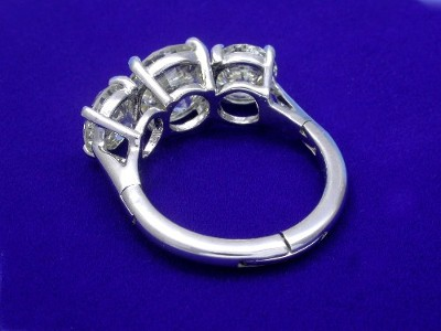 Round brilliant cut diamond prong set in a platinum three-stone mounting with two round brilliant side diamonds, classic basket-style heads, and expandable shank
